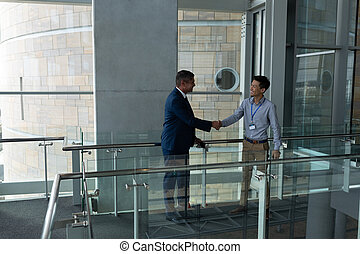 Handshake between an Asian businessman and a Caucasian businessman on the walkway of the first floor