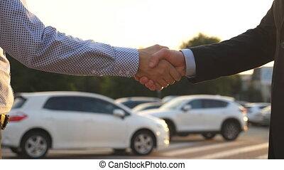 Handshake between two business men outdoor. Male hands in...
