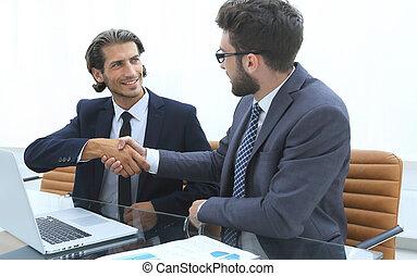 handshake business man sitting behind a Desk.