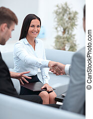 handshake business partners in the office.