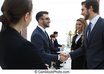 handshake business partners in the office