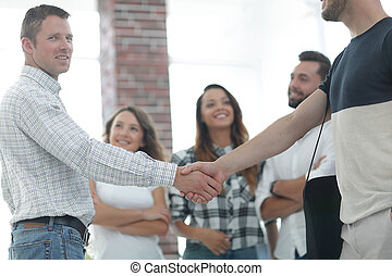 handshake business partners in the creative office.the...