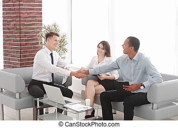 handshake business partners in the spacious office