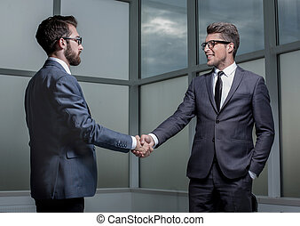 handshake business partners standing in the office.