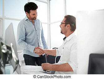 handshake business people in a modern office.