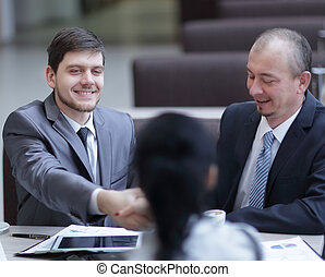 handshake Manager and customer in a modern office.