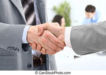 handshake of business partners after striking deal
