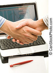 Handshake of business people on the background of laptop