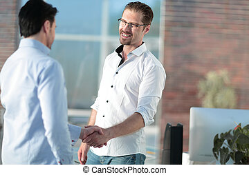 handshake of business people standing in a creative office