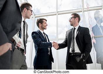 handshake of business people standing in modern office