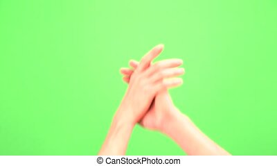 Handshake of male hands on a green background or chromakey.