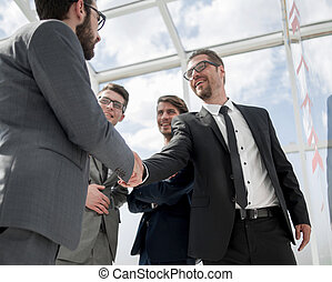 handshake of serious business partners standing in the office