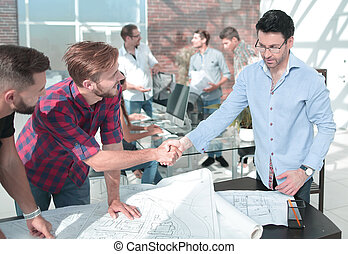 handshake of the architect and contractor over a work Des