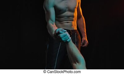 Handshake of two athletic muscular men on a black studio background. Slow motion. Close up
