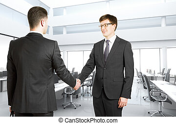 Handshake of two businessmen in a bright modern office