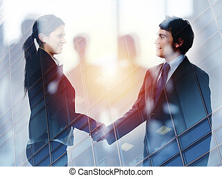 Handshake of two businessperson in office concept of partnership and teamwork. double exposure