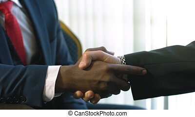 Handshake of two multiracial men in suits as sign of trusted...