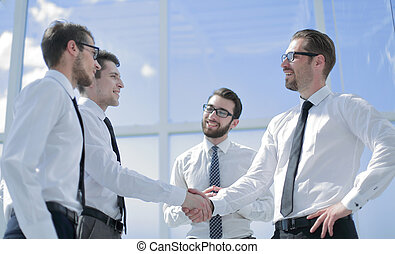 handshake of young business partners standing in the office