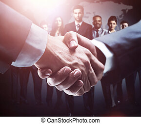 handshake on the background group of business people in dark...