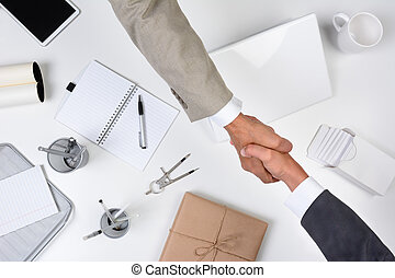 Two men reaching over a desk to shake hands. Shot from a high angle the desk is white as are most of the office items except for a brown wrapped package.