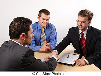Businessmen negotiating and signing a contract.