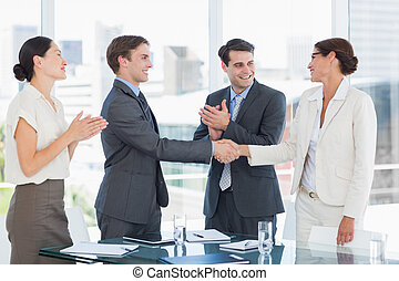 Handshake to seal a deal after a job recruitment meeting in an office