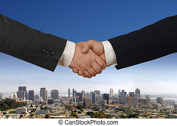 Handshake - Two businessmen shaking hands with daytime city...