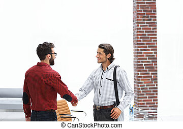 handshake two employees standing in the office