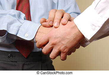 handshake - two young manager shaking hands with each other