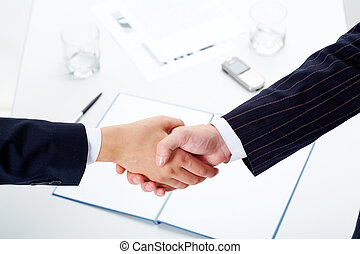 Handshake - Woman and man shaking hands over paper, pen, ...