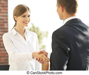 handshake young business woman with a colleague