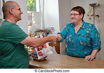 Handshaking in einem Geschaeft - Frau verabschiedet sich mit...