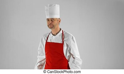 Handsome adult chef turns, he crosses his arms and nods his head on a gray background