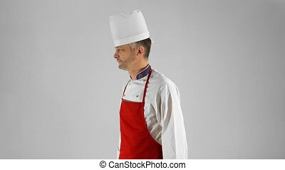 Handsome adult chef turns, he crosses his arms with knive and nods his head on a gray background