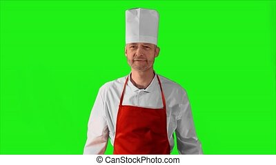 Handsome adult chef turns, he crosses his arms with knives and nods his head on a green background