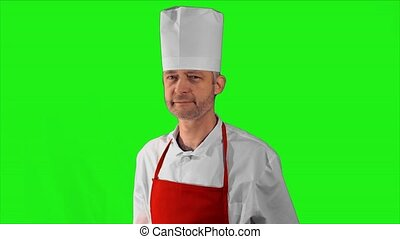 Handsome adult chef turns, he crosses his arms and nods his head close-up on a green background