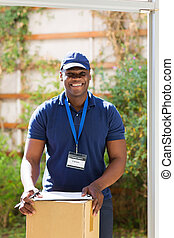 african american delivery man with a parcel standing at the door