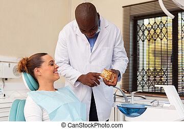 african american dentist explaining teeth model to patient