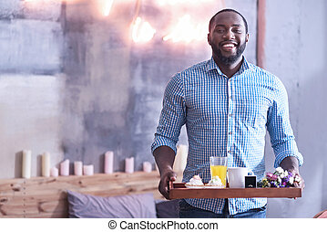 Handsome African American man holding breakfast tray in the bedroom