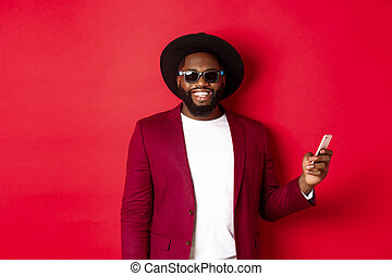 Handsome african american man shopping online, making an order on smartphone and smiling, standing over red background