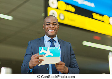 african businessman holding air ticket - handsome african...
