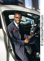 Handsome african car salesman standing at the dealership holding a tablet