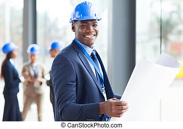 handsome african construction engineer with blue print