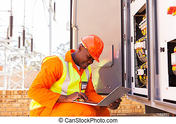 african electrical engineer working on laptop - handsome ...