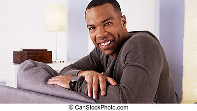 Handsome African man sitting on couch