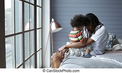 Handsome african man talking to his son in bedroom