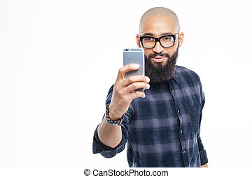 Handsome african man with beard taking selfie using smartphone