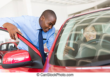 african salesman explaining car features to potential customer
