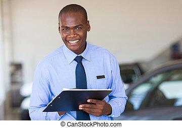 african salesman working at vehicle showroom