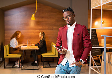Handsome African student or contemporary businessman with touchpad